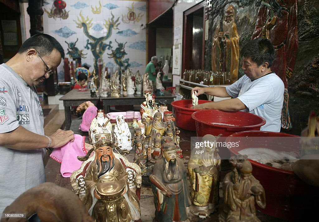 This photo taken on February 6, 2013 shows Indonesian devotees washing religious statues and figurines at a Buddhist temple in Surabaya, located in Indonesia's East Java province, in preparation for the Chinese Lunar New Year celebration. The 'Year of the Snake' falls across the region on February 10. AFP PHOTO / JUNI KRISWANTO