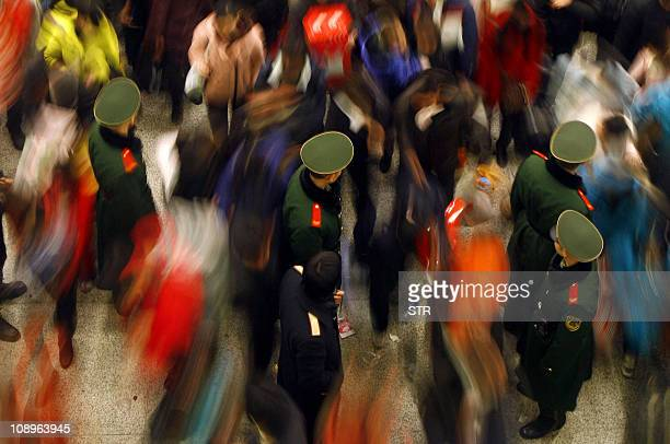 This photo taken on February 9 2011 shows thousands of passengers carrying their belongings walking out of a railway station as they return to work...