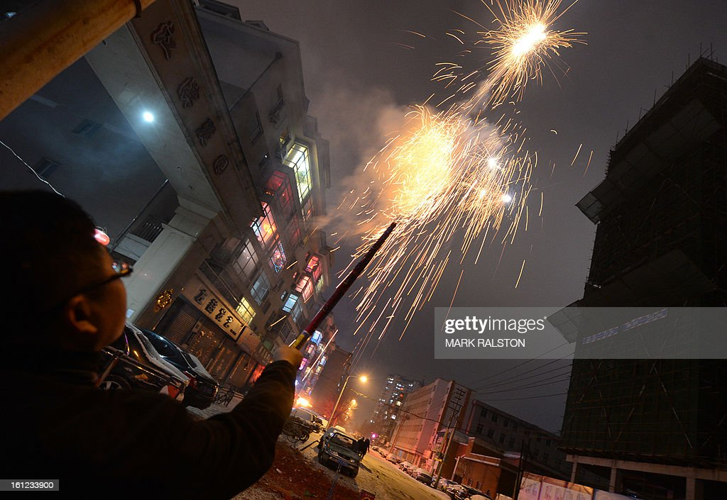 This photo taken on February 9, 2013 shows a Chinese man letting off fireworks to welcome in the 'Year of the Snake' during the Lunar New Year celebrations in the Chinese border town of Dandong