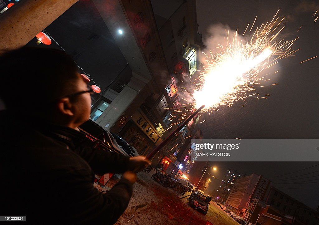 This photo taken on February 9, 2013 shows a Chinese man letting off fireworks to welcome in the 'Year of the Snake' during the Lunar New Year celebrations in the Chinese border town of Dandong. Revellers across the city lit fireworks and prayed as China traditionally welcomed in the new year. AFP PHOTO/Mark RALSTON