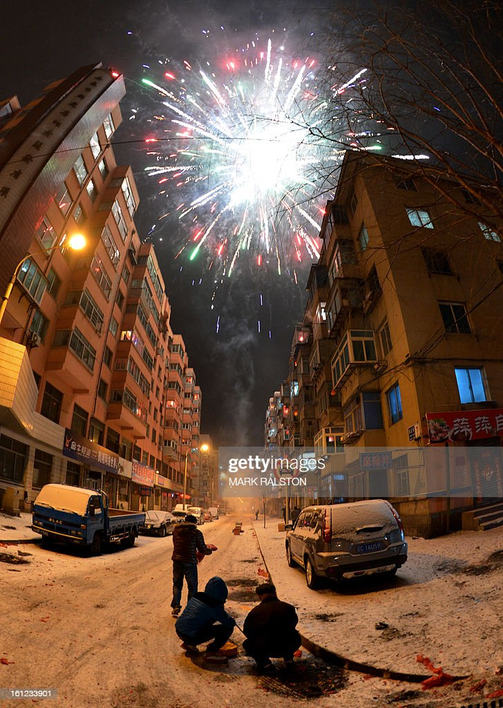 This photo taken on February 9, 2013 shows Chinese men letting off fireworks to welcome in the 'Year of the Snake' during the Lunar New Year celebrations in the Chinese border town of Dandong. Revellers across the city lit fireworks and prayed as China traditionally welcomed in the new year. AFP PHOTO/Mark RALSTON