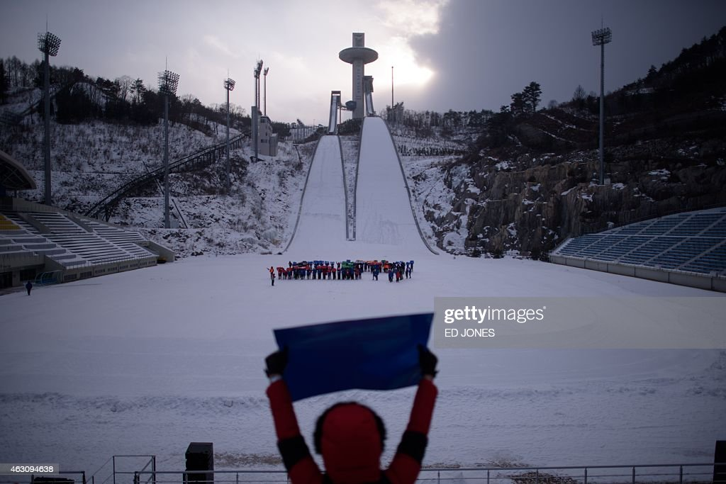 This photo taken on February 9 2015 shows a woman holding up a placard a participants rehearse in the ski jump field for a performance event marking...