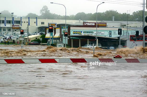 This photo taken on January 10 2011 shows flood waters surging across the railway tracks towards shops as flash floods inundate the city of Toowoomba...