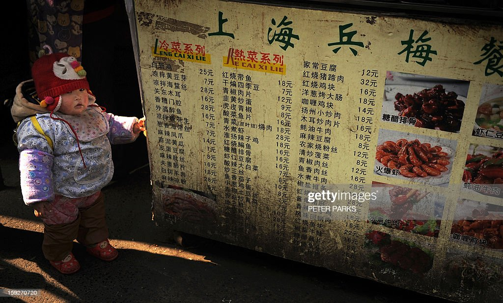 This photo taken on January 10, 2013 shows a baby standing next to a menu at a food stall on a street in Shanghai. China's inflation rate slowed to 2.6 percent in 2012, the National Bureau of Statistics said on January 11, down sharply from 5.4 percent the year before. AFP PHOTO/Peter PARKS