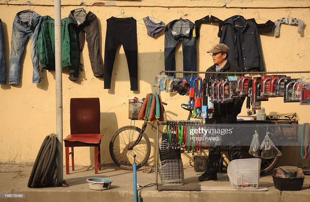 This photo taken on January 10, 2013 shows a bicycle repairman waiting for customers on a street in Shanghai. China's inflation rate slowed to 2.6 percent in 2012, the National Bureau of Statistics said, down sharply from 5.4 percent the year before. AFP PHOTO/Peter PARKS