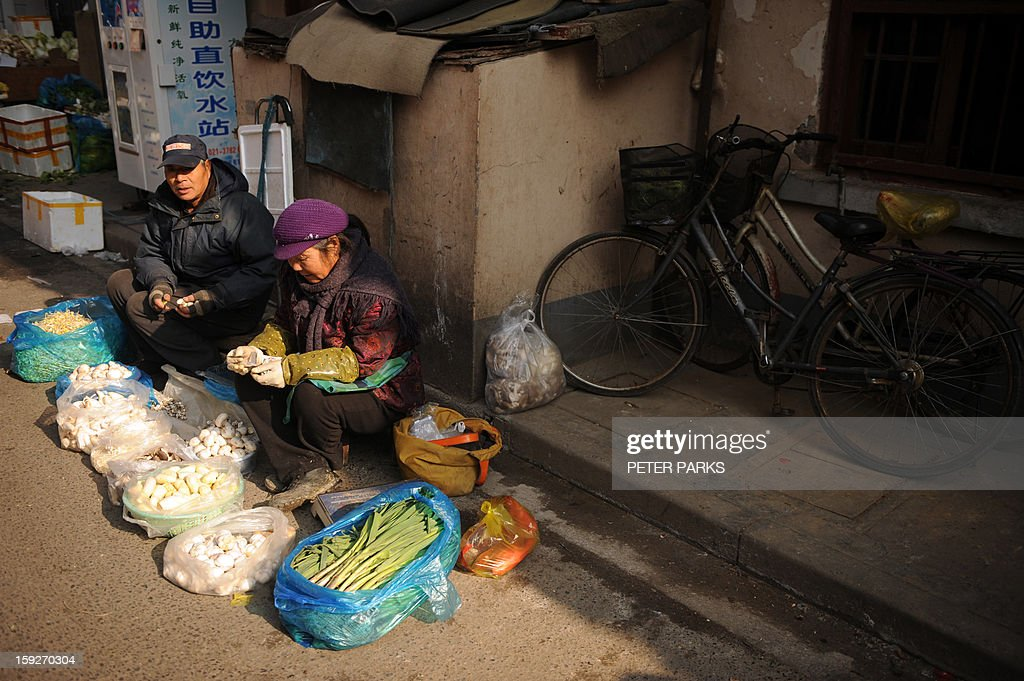 This photo taken on January 10, 2013 shows a couple selling vegetables on a street in Shanghai. China's inflation rate slowed to 2.6 percent in 2012, the National Bureau of Statistics said, down sharply from 5.4 percent the year before. Peter PARKS