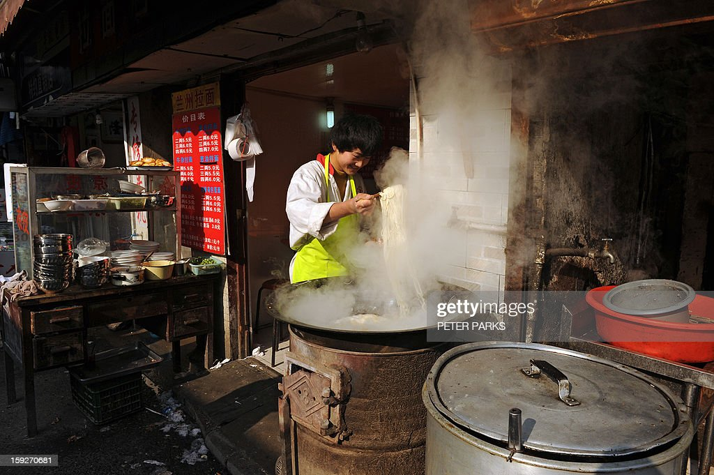 This photo taken on January 10, 2013 shows a man cooking noodles on a street in Shanghai. China's inflation rate slowed to 2.6 percent in 2012, the National Bureau of Statistics said, down sharply from 5.4 percent the year before. AFP PHOTO/Peter PARKS