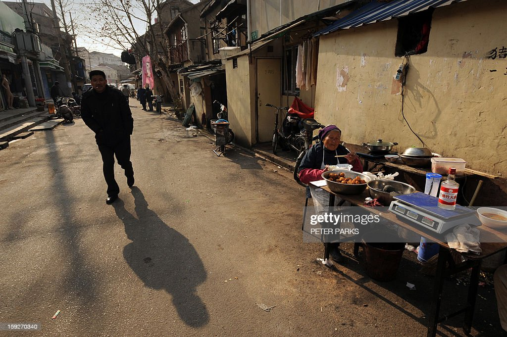 This photo taken on January 10, 2013 shows a man (L) walking past a woman (R) selling fruit on a street in Shanghai. China's inflation rate slowed to 2.6 percent in 2012, the National Bureau of Statistics said, down sharply from 5.4 percent the year before. AFP PHOTO/Peter PARKS
