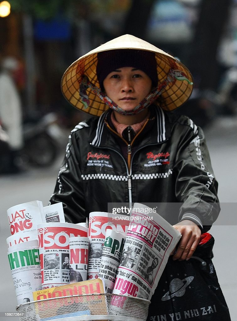 This photo taken on January 10, 2013 shows a newspaper vendor riding a bicycle along a street in downtown Hanoi. At a recent national meeting on propaganda works, propaganda officials revealed they prepared hundreds of 'online writers' to deal with the current online anti-state propaganda led by dissident bloggers. Last month Prime Minister Nguyen Tan Dung ordered a new crackdown on online dissent. AFP PHOTO / HOANG DINH Nam