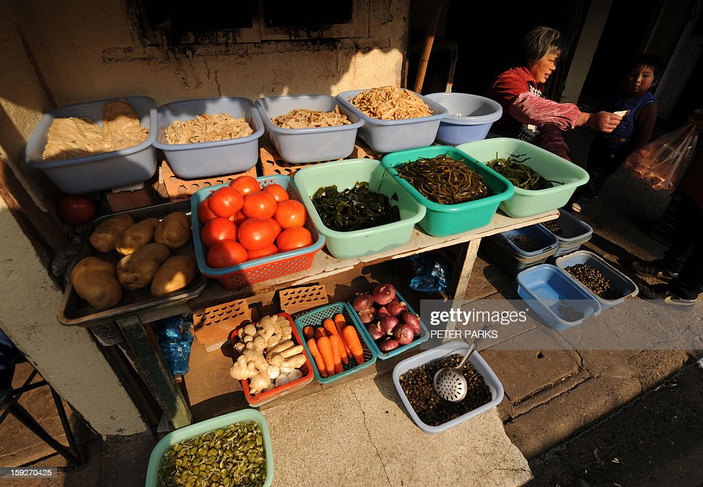 This photo taken on January 10, 2013 shows a woman (R) selling fruit and vegetables on a street in Shanghai. China's inflation rate slowed to 2.6 percent in 2012, the National Bureau of Statistics said, down sharply from 5.4 percent the year before. AFP PHOTO/Peter PARKS