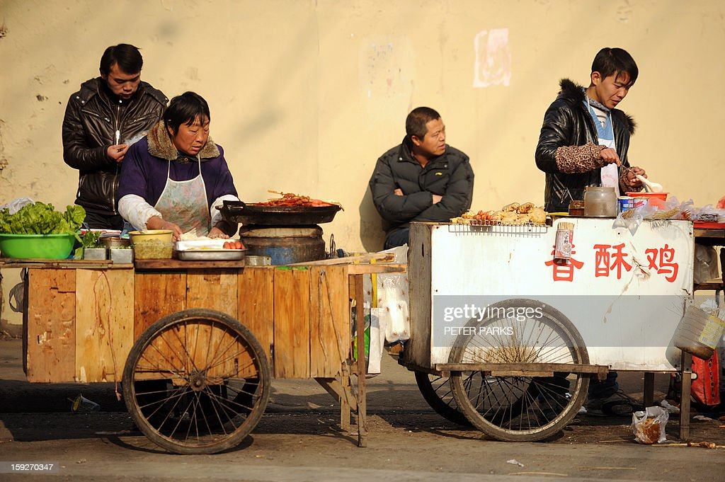 This photo taken on January 10, 2013 shows vendors selling food on a street in Shanghai. China's inflation rate slowed to 2.6 percent in 2012, the National Bureau of Statistics said, down sharply from 5.4 percent the year before. AFP PHOTO/Peter PARKS