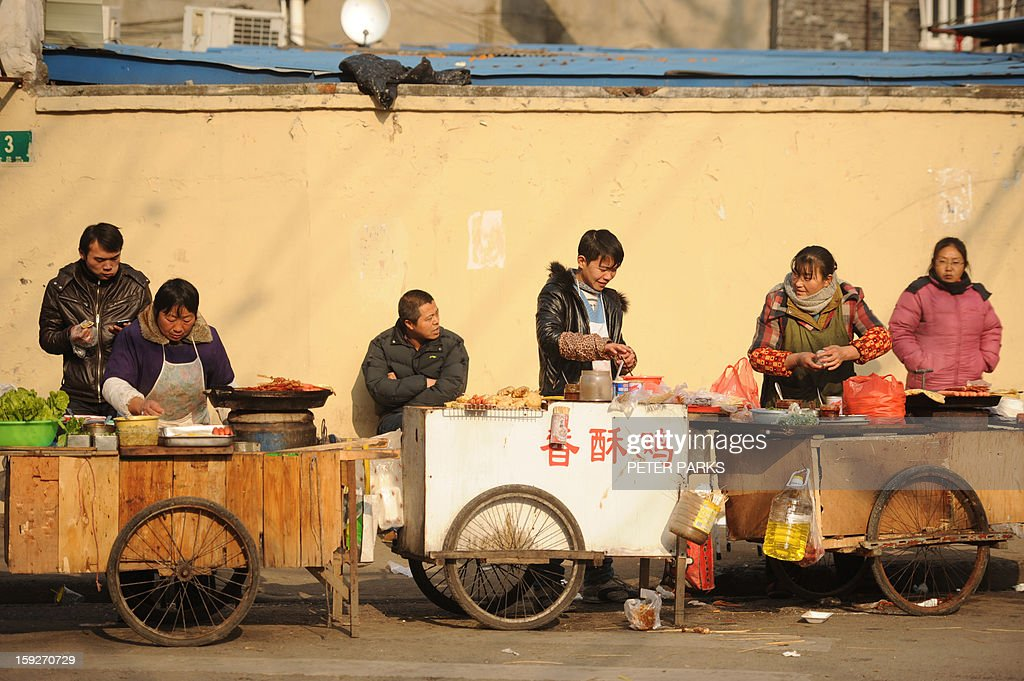 This photo taken on January 10, 2013 shows vendors selling food on a street in Shanghai. China's inflation rate slowed to 2.6 percent in 2012, the National Bureau of Statistics said on January 11, down sharply from 5.4 percent the year before. AFP PHOTO/Peter PARKS