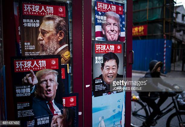 This photo taken on January 10 2017 shows a cyclist riding past advertisements for a magazine showing various cover stories including ones featuring...