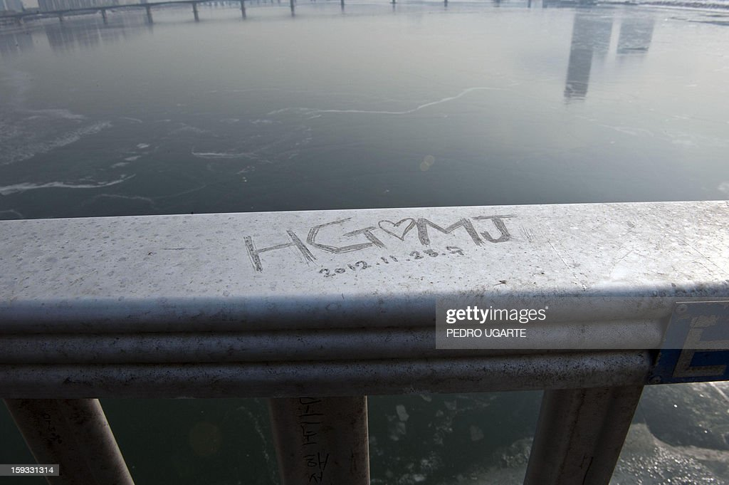 This photo taken on January 11, 2013 shows a love message scrawled on Mapo Bridge -a common site for suicides- over Seoul's Han river. The South Korean capital has installed anti-suicide monitoring devices on bridges over the city after 196 people jumped to their deaths on 2012 according to South Korean officials. The new initiative -- in a country with the highest suicide rate among leading developed nations -- incorporates closed-circuit television cameras programmed to recognize motions that suggest somebody might be preparing to jump from a bridge. AFP PHOTO / Pedro UGARTE