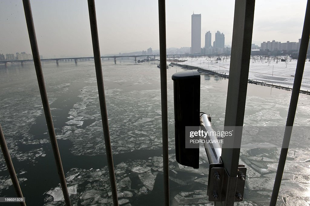 This photo taken on January 11, 2013 shows an anti-suicide monitoring device installed at Mapo Bridge - a common place for suicides- over Seoul's Han river. The South Korean capital has installed anti-suicide monitoring devices on bridges over the city after 196 people jumped to their deaths on 2012 according to South Korean officials. The new initiative -- in a country with the highest suicide rate among leading developed nations -- incorporates closed-circuit television cameras programmed to recognize motions that suggest somebody might be preparing to jump from a bridge. AFP PHOTO / Pedro UGARTE