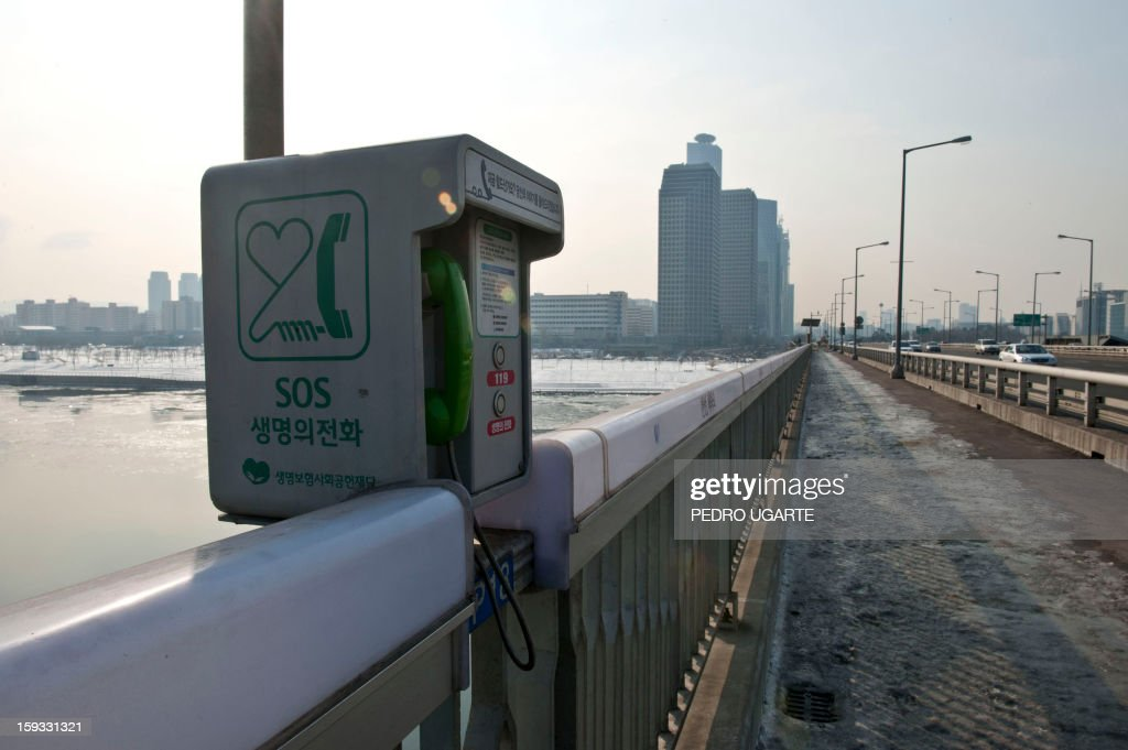 This photo taken on January 11, 2013 shows an emergency telephone placed by the government at Mapo Bridge -a common site for suicides- over Seoul's Han river. The South Korean capital has installed anti-suicide monitoring devices on bridges over the city after 196 people jumped to their deaths on 2012 according to South Korean officials. The new initiative -- in a country with the highest suicide rate among leading developed nations -- incorporates closed-circuit television cameras programmed to recognize motions that suggest somebody might be preparing to jump from a bridge. AFP PHOTO / Pedro UGARTE