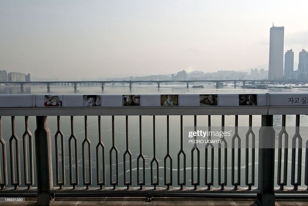 This photo taken on January 11, 2013 shows pictures of children placed by the government to dissuade potential suicides along the railing at Mapo Bridge -a common site for suicides- over Seoul's Han river. The South Korean capital has installed anti-suicide monitoring devices on bridges over the city after 196 people jumped to their deaths on 2012 according to South Korean officials. The new initiative -- in a country with the highest suicide rate among leading developed nations -- incorporates closed-circuit television cameras programmed to recognize motions that suggest somebody might be preparing to jump from a bridge. AFP PHOTO / Pedro UGARTE