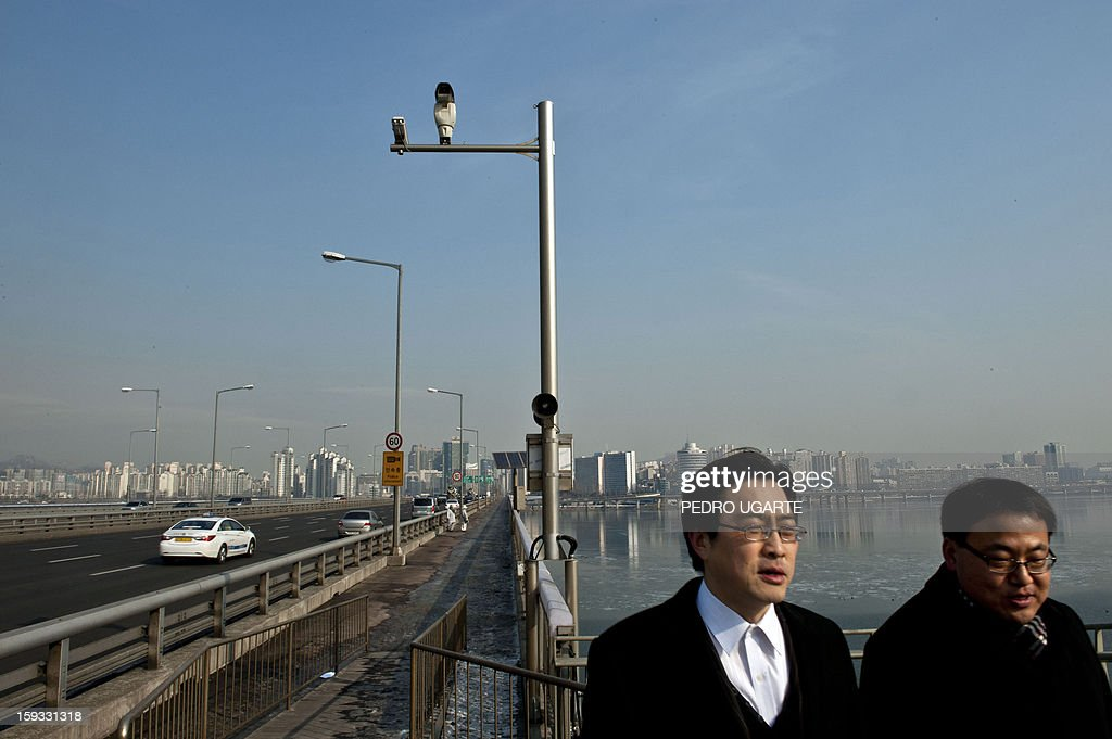 This photo taken on January 11, 2013 shows two people walking under a CCTV camera (C) placed by the government to monitor Mapo Bridge -a common site for suicides- over Seoul's Han river. The South Korean capital has installed anti-suicide monitoring devices on bridges over the city after 196 people jumped to their deaths on 2012 according to South Korean officials. The new initiative -- in a country with the highest suicide rate among leading developed nations -- incorporates closed-circuit television cameras programmed to recognize motions that suggest somebody might be preparing to jump from a bridge. AFP PHOTO / Pedro UGARTE