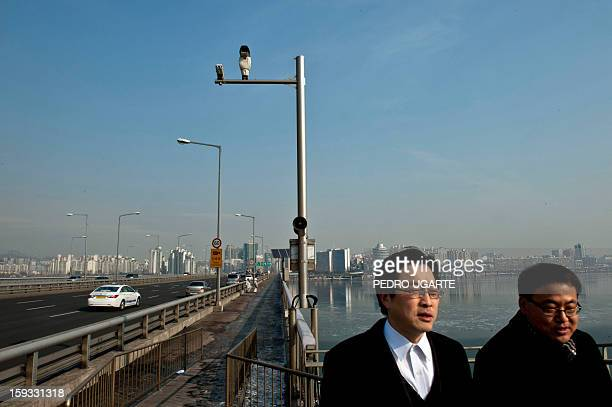 This photo taken on January 11 2013 shows two people walking under a CCTV camera placed by the government to monitor Mapo Bridge a common site for...