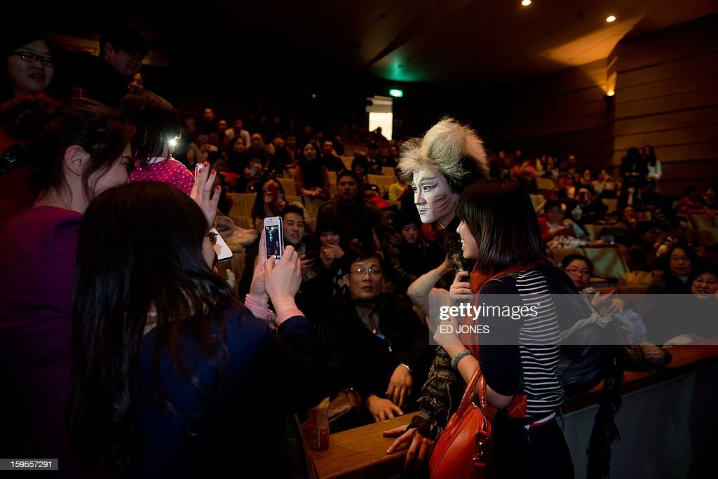 This photo taken on January 15, 2013 shows a cast member posing with the audience following a Chinese performance of 'Cats' at the Century Theatre in Beijing. Featuring a kung-fu cat, and a set design that includes bird cages and Peking duck, the culturally adapted Mandarin version of British composer Andrew Lloyd Webber's hit musical 'Cats' is hoping to bring West End success to the far east. The show, which runs until February 3, is on the final leg of a country-wide tour after passing through Shanghai, Chonqing, and Guangzhou. Western musicals have traditionally been rare in China with 'Cats' following its compatriot spectacle 'Mamma Mia!' as the country's second localised large-scale musical theatre production. AFP PHOTO / Ed Jones