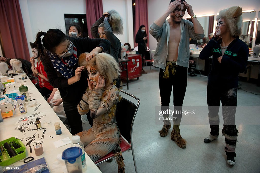 This photo taken on January 15, 2013 shows cast members applying make-up prior to a Chinese performance of 'Cats' at the Century Theatre in Beijing. Featuring a kung-fu cat, and a set design that includes bird cages and Peking duck, the culturally adapted Mandarin version of British composer Andrew Lloyd Webber's hit musical 'Cats' is hoping to bring West End success to the far east. The show, which runs until February 3, is on the final leg of a country-wide tour after passing through Shanghai, Chonqing, and Guangzhou. Western musicals have traditionally been rare in China with 'Cats' following its compatriot spectacle 'Mamma Mia!' as the country's second localised large-scale musical theatre production. AFP PHOTO / Ed Jones