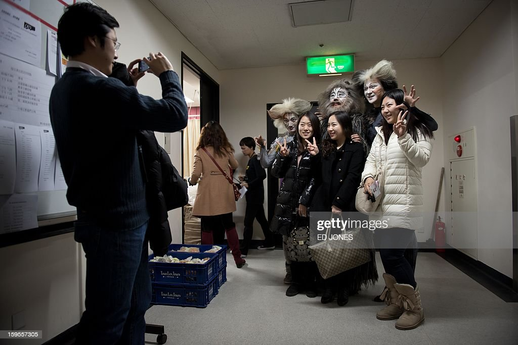 This photo taken on January 15, 2013 shows cast members posing with fans following a Chinese performance of 'Cats' at the Century Theatre in Beijing. Featuring a kung-fu cat, and a set design that includes bird cages and Peking duck, the culturally adapted Mandarin version of British composer Andrew Lloyd Webber's hit musical 'Cats' is hoping to bring West End success to the far east. The show, which runs until February 3, is on the final leg of a country-wide tour after passing through Shanghai, Chonqing, and Guangzhou. Western musicals have traditionally been rare in China with 'Cats' following its compatriot spectacle 'Mamma Mia!' as the country's second localised large-scale musical theatre production. AFP PHOTO / Ed Jones
