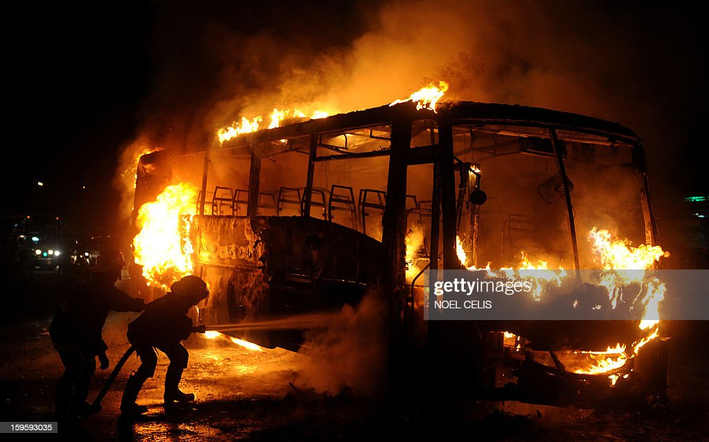 This photo taken on January 16, 2013 shows firefighters extinguishing the flames after a passenger bus caught fire in Manila. Six passengers were injured according to local media reports. AFP PHOTO / NOEL CELIS