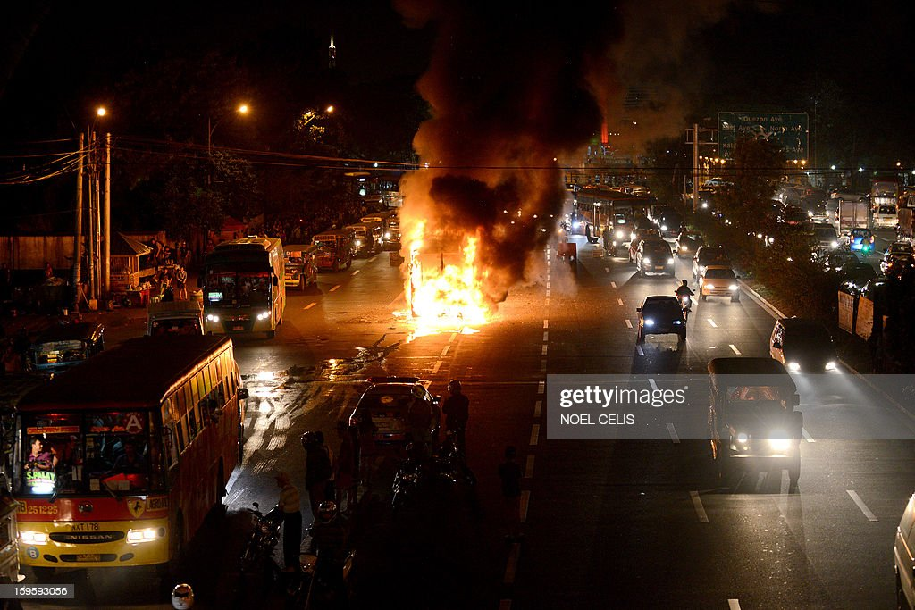 This photo taken on January 16, 2013 shows firefighters extinguishing the flames after a passenger bus caught fire in the middle of a street in Manila. Six passengers were injured according to local media reports.