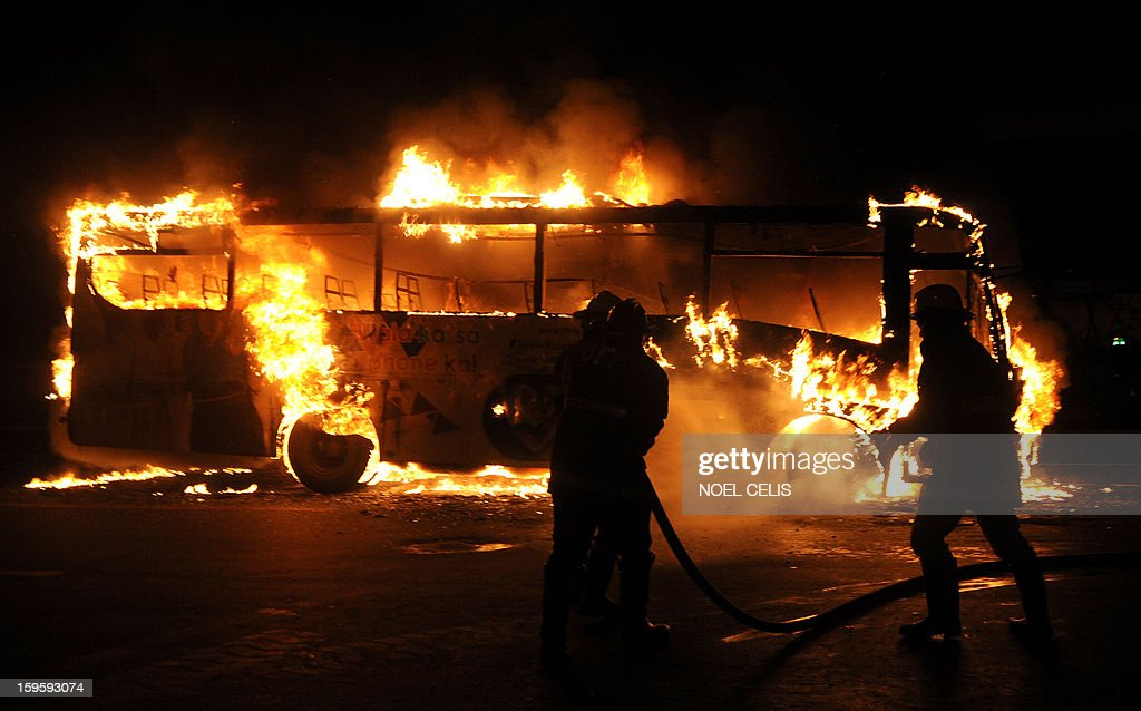 This photo taken on January 16, 2013 shows firefighters extinguishing the flames after a passenger bus caught fire in Manila. Six passengers were injured according to local media reports.