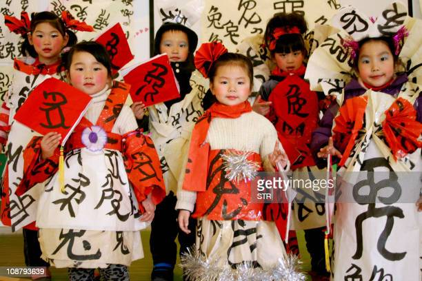 This photo taken on January 17 2011 shows Chinese children posing while dressed up in costumes with calligraphy written with the Chinese characters...