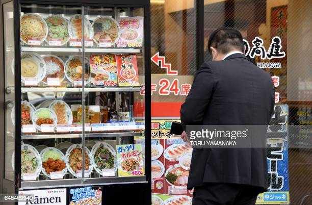 This photo taken on January 19 2017 shows a customer looking at a display of fake food dishes at the window of a Chinese restaurant in Tokyo They may...