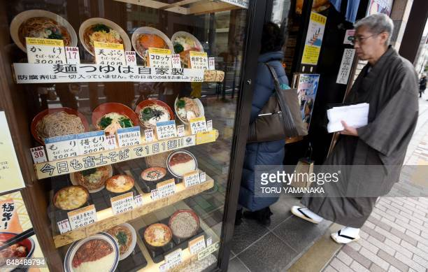 This photo taken on January 19 2017 shows customers entering a Japanese restaurant with a presentation of fake food dishes displayed in front of the...