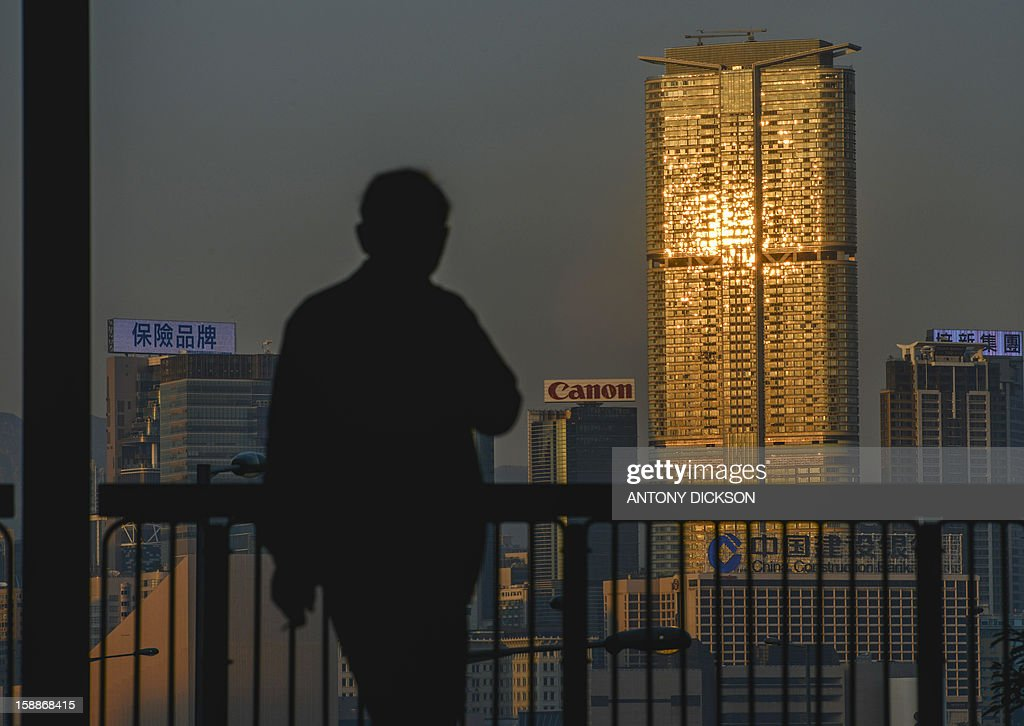 This photo taken on January 2, 2013 shows a pedestrian walking in front of a building lit up by the setting sun in Hong Kong. Home prices in the Asian financial hub have skyrocketed 90 percent since 2009 due to an influx of wealthy mainland Chinese buyers, pushing home-ownership beyond the reach of many of its seven million people. AFP PHOTO / Antony DICKSON