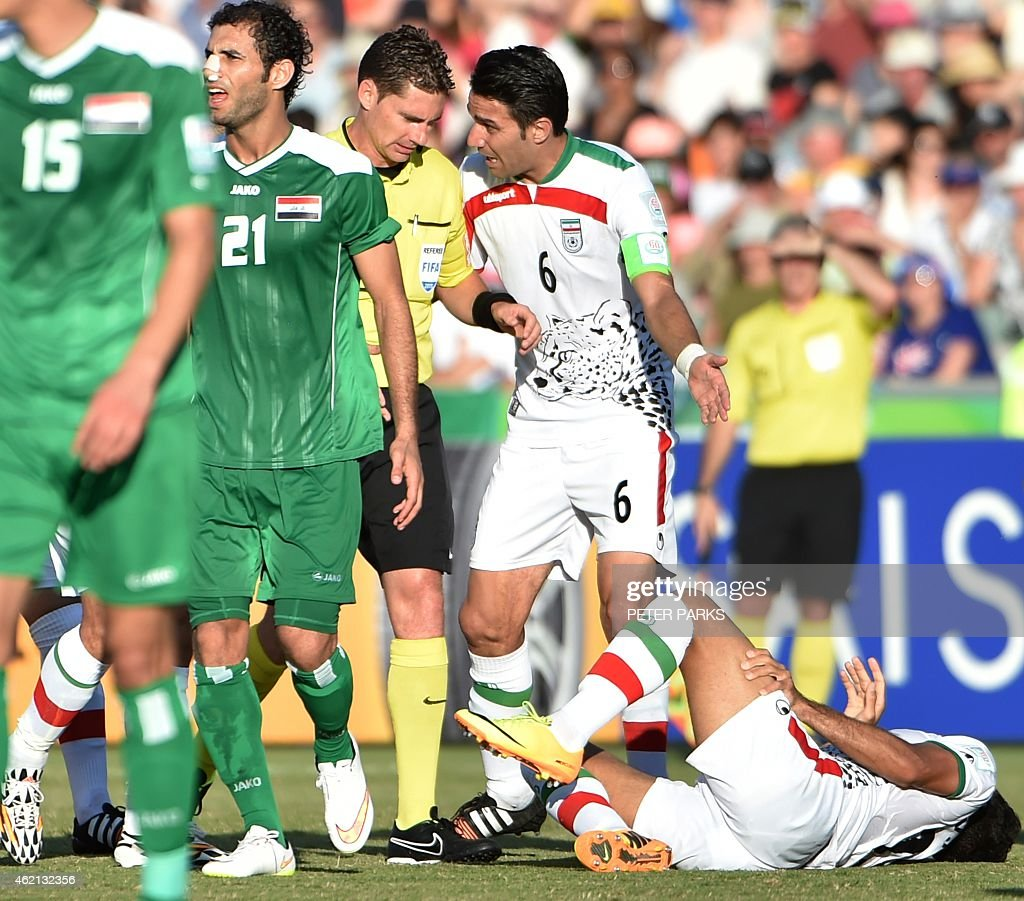 This photo taken on January 23, 2015 shows Javad Nekonam (C-R) of Iran talking to Australian referee Ben Williams (C-L) during their AFC Asian Cup quarter-final football match against Iraq in Canberra. A top Iranian official on January 25 called for a life ban for referee Williams after a bungling display in their Asian Cup quarter-final loss to Iraq. AFP PHOTO/Peter PARKS --IMAGE