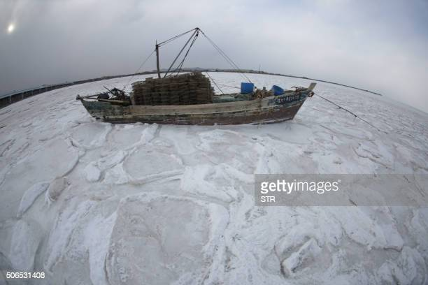 TOPSHOT This photo taken on January 23 2016 shows a ship stuck in the ice after coastal waters froze in Dalian in northeast China's Liaoning province...