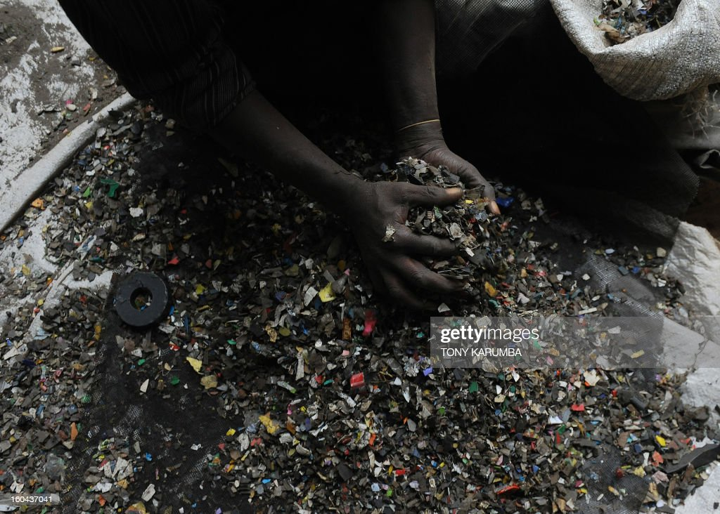 This photo taken on January 30, 2013, shows a worker at the Eco-post Recycling company factory in Nairobi collecting pulverized plastic waste before sending it to be pulverized and later molten to make fencing posts from recycled plastics.The city of Nairobi generates over 2,800 metric tonnes of waste every day, 20% being plastic. Most of this is disposed off crudely resulting in heaps of garbage littering streets and open fields. In addittion, 222,000 acres of Kenya's main water catchment forest, the Mau, has suffered tremendous loss as demand for timber has soared due to the rapidly growing housing market. Ecopost is involved in recycling plastic litter as a cheap and environmentally friendly alternative to habitat loss, littering the streets that clogs sewers and creates hazardous living conditions into aesthetic, durable and environmentally friendly fencing posts. AFP PHOTO / Tony KARUMBA