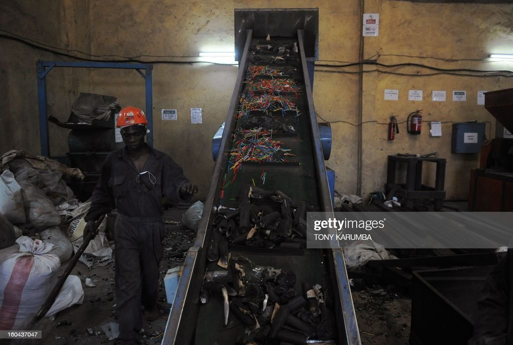 This photo taken on January 30, 2013, shows a worker at the Eco-post Recycling company factory in Nairobi loading plastic waste onto a conveyor belt before sending it to be pulverized and later molten to make fencing posts from recycled plastics.The city of Nairobi generates over 2,800 metric tonnes of waste every day, 20% being plastic. Most of this is disposed off crudely resulting in heaps of garbage littering streets and open fields. In addittion, 222,000 acres of Kenya's main water catchment forest, the Mau, has suffered tremendous loss as demand for timber has soared due to the rapidly growing housing market. Ecopost is involved in recycling plastic litter as a cheap and environmentally friendly alternative to habitat loss, littering the streets that clogs sewers and creates hazardous living conditions into aesthetic, durable and environmentally friendly fencing posts. AFP PHOTO / Tony KARUMBA