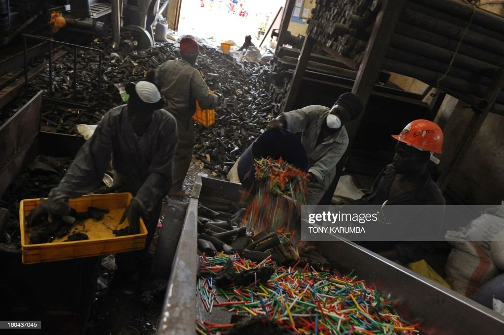 This photo taken on January 30, 2013, shows workers at the Eco-post Recycling company factory in Nairobi loading plastic waste onto a conveyor belt before sending it to be pulverized and later molten to make fencing posts from recycled plastics.The city of Nairobi generates over 2,800 metric tonnes of waste every day, 20% being plastic. Most of this is disposed off crudely resulting in heaps of garbage littering streets and open fields. In addittion, 222,000 acres of Kenya's main water catchment forest, the Mau, has suffered tremendous loss as demand for timber has soared due to the rapidly growing housing market. Ecopost is involved in recycling plastic litter as a cheap and environmentally friendly alternative to habitat loss, littering the streets that clogs sewers and creates hazardous living conditions into aesthetic, durable and environmentally friendly fencing posts. AFP PHOTO / Tony KARUMBA