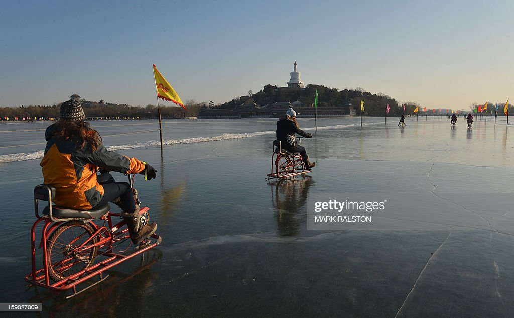 This photo taken on January 5, 2013 shows children riding ice bikes on the frozen historic Beihai Lake in Beijing. The lake which was once the playground of China's emperors and empresses now attracts scores of tourists and locals who use its frozen surface for skating, ice biking and exercising, despite winter temperatures of up to minus 18 Celsius temperatures. AFP PHOTO/Mark RALSTON