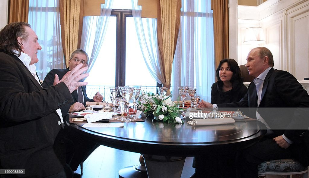 This photo taken on January 5, 2013 shows French actor Gerard Depardieu (L) speaking to Russian President Vladimir Putin (R) during their meeting at Putin's residence in Sochi. Depardieu has received a Russian passport, Putin's spokesman said on January 6.
