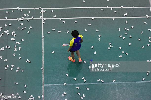 TOPSHOT This photo taken on January 6 2016 shows a player walking amongst shuttlecocks during a training session with the Beijing Badminton team in...