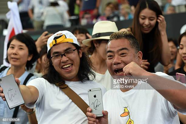 This photo taken on January 6 2017 shows Japanese comedians Roch Nakaokal and Tetsuro Degawa displaying their autographed mobile phone signed by...