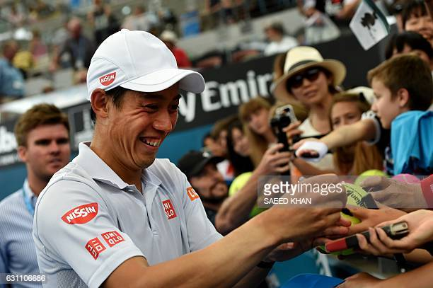 This photo taken on January 6 2017 shows Japan's Nei Nishikori laughing on a joke cracked by Japanese comedian Tetsuro Degawa after his victory over...