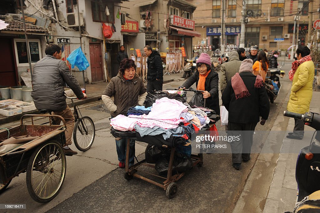This photo taken on January 9, 2013 shows a woman peddling her wares on a street in Shanghai. China's trade surplus surged 48.1 percent to 231.1 billion USD in 2012 from the previous year, though total trade volume grew at a much slower pace, official data showed. AFP PHOTO/Peter PARKS