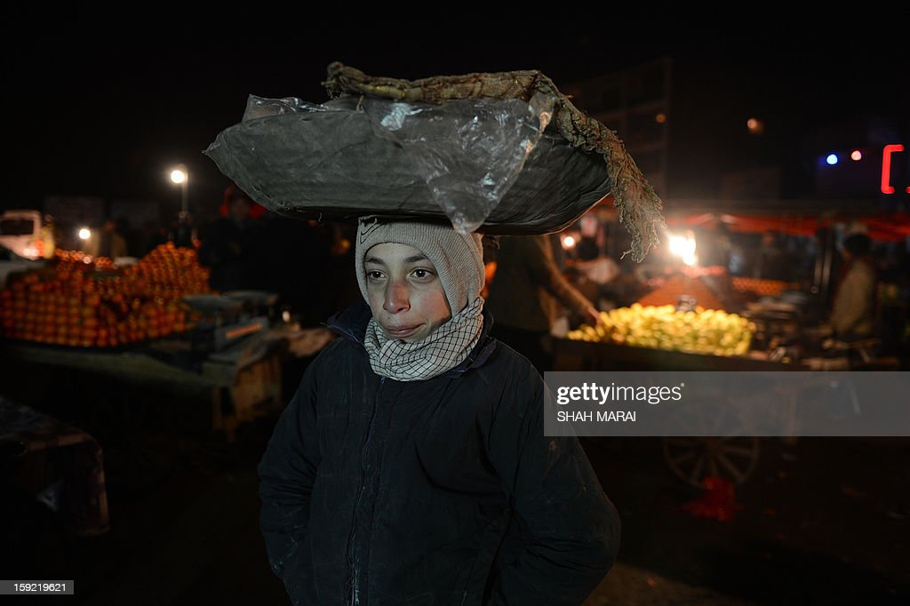 This photo taken on January 9, 2013 shows a young Afghan street vendor named Yonis, 12, carrying a basket of 'bolani', a traditional Afghan food, on his head at a busy market on a cold day in Kabul. Despite Afghanistan receiving billions of dollars of aid since 2001, more than 100 children died last year during the harshest winter in two decades, and the UN refugee agency UNHCR has co-ordinated efforts to reduce repeat fatalities, it was reported on January 2. AFP PHOTO / SHAH Marai