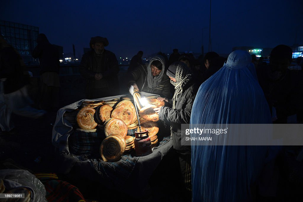 This photo taken on January 9, 2013 shows an Afghan man buying bread from a vendor at a busy market on a cold day in Kabul. Despite Afghanistan receiving billions of dollars of aid since 2001, more than 100 children died last year during the harshest winter in two decades, and the UN refugee agency UNHCR has co-ordinated efforts to reduce repeat fatalities, it was reported on January 2. AFP PHOTO / SHAH Marai