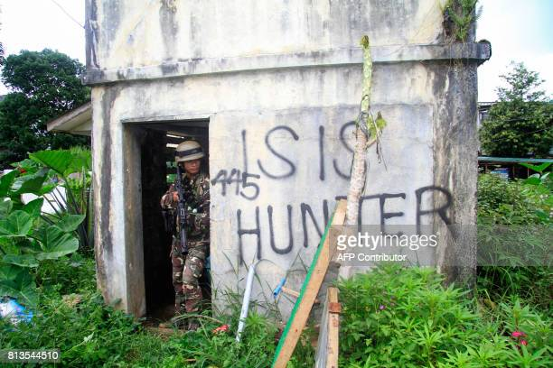 This photo taken on July 12 2017 shows a Philippine soldier taking cover as they advance to the frontline where they are battling militants in Marawi...