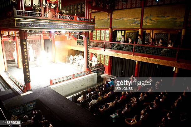 This photo taken on July 13 2012 shows members of an audience watching a performance at the Temple Theatre of Beijing Opera House Following its...