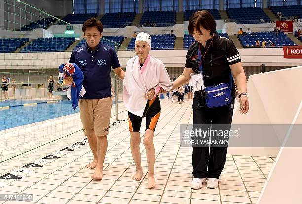 This photo taken on July 14 2016 shows an official and Shintaro Sawada the coach of Mieko Nagaoka helping the 101yearold swimmer at the poolside...