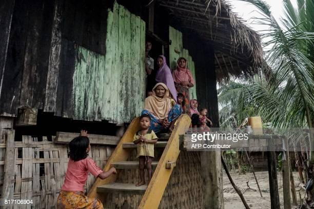 This photo taken on July 14 2017 shows a Muslim family sitting in front of their house at Maung Hnama village Buthidaung township in Myanmar's...
